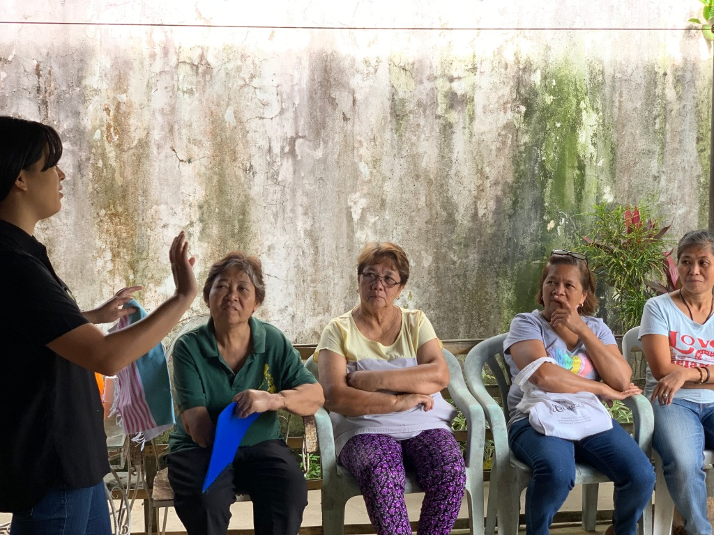 Yvette, Co-founder of WVN, explains to the weavers in Indang